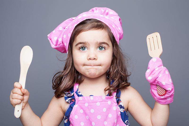 little girl holding utensils